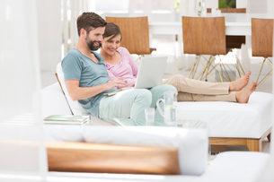 Couple using laptop together on daybed in modern living roomの写真素材 [FYI02163003]