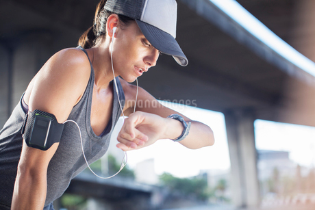 Woman looking at watch after exercising on city streetの写真素材 [FYI02163014]