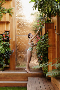 Woman reaching for plant in wooden courtyardの写真素材 [FYI02163038]