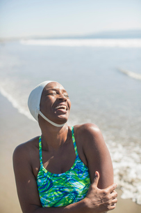 Woman in bathing suit and cap laughing on beachの写真素材 [FYI02163064]