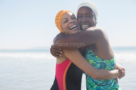 Enthusiastic women hugging in bathing suits and capsの写真素材 [FYI02163071]