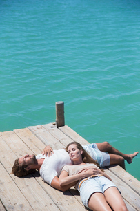 Couple relaxing together on wooden dockの写真素材 [FYI02163117]
