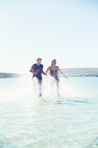 Couple splashing in water on beachの写真素材 [FYI02163195]