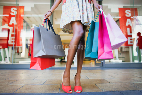 Woman carrying shopping bags in shopping mallの写真素材 [FYI02163214]