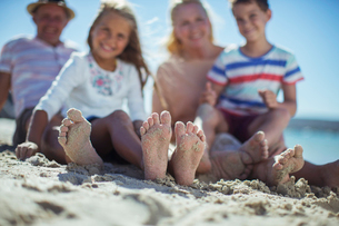 Family sitting together with feet in sandの写真素材 [FYI02163287]