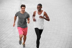Men running through city streets togetherの写真素材 [FYI02163352]