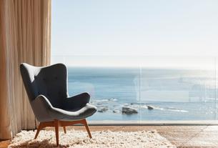 Chair in sunny window overlooking oceanの写真素材 [FYI02163391]