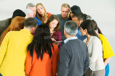 Business people huddled around businesswoman with laptopの写真素材 [FYI02163587]