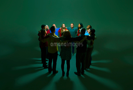 Business people in circle around bright lightの写真素材 [FYI02163606]
