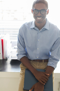 Portrait of smiling young man wearing glasses and blue shirt leaning on desk in officeの写真素材 [FYI02163658]