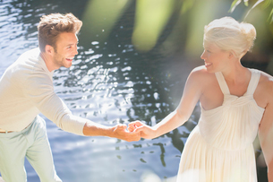 Couple holding hands by pool outdoorsの写真素材 [FYI02163673]
