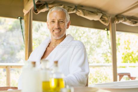 Man wearing bathrobe at tableの写真素材 [FYI02163697]