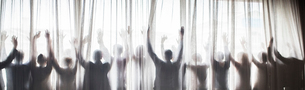 Silhouette of people raising hands behind transparent curtainの写真素材 [FYI02163738]