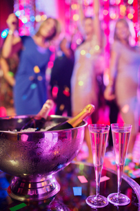 Champagne bottles in ice bucket and champagne flutes in nightclub, people dancing in backgroundの写真素材 [FYI02163745]