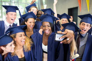 Group of smiling students in graduation gowns taking selfie on graduation dayの写真素材 [FYI02163764]