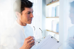 looking away,View of man in laboratory holding glasses and chartの写真素材 [FYI02163773]