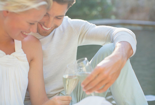Couple toasting each other with champagne outdoorsの写真素材 [FYI02163776]