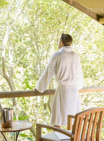 Man wearing bathrobe on balconyの写真素材 [FYI02163837]