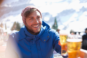 Smiling man in warm clothing drinking beer outdoorsの写真素材 [FYI02163850]