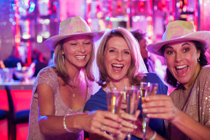Portrait of three cheerful women wearing cowboy hats toasting with champagne flutes in nightclubの写真素材 [FYI02163865]