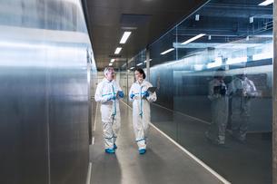 Scientists in clean suits walking in hallwayの写真素材 [FYI02163885]