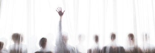 Silhouette of people behind transparent curtain, one person rising handの写真素材 [FYI02163906]