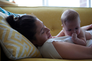 View of mother lying on sofa with little baby sucking thumbの写真素材 [FYI02163947]