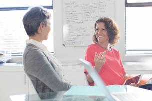 Two smiling women talking in office, whiteboard in backgroundの写真素材 [FYI02163952]