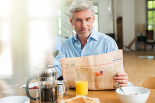 Older man reading newspaper at breakfast tableの写真素材 [FYI02163993]