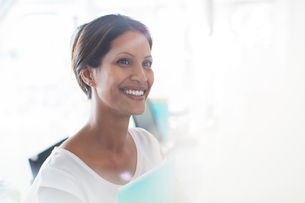 Portrait of smiling woman holding documents in officeの写真素材 [FYI02164005]
