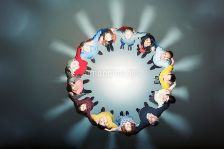 Business people forming huddle around bright lightの写真素材 [FYI02164063]