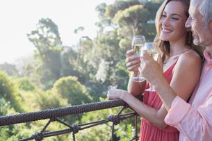 Couple toasting each other on balconyの写真素材 [FYI02164091]