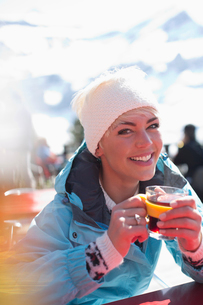 Portrait of smiling woman in warm clothing drinking teaの写真素材 [FYI02164098]