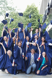 Group portrait of students in graduation gowns throwing mortarboards in the airの写真素材 [FYI02164102]