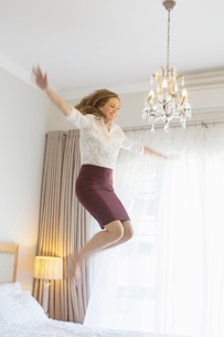 Businesswoman jumping on bed in hotel roomの写真素材 [FYI02164115]