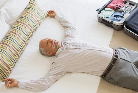Businessman laying on bed in hotel roomの写真素材 [FYI02164132]