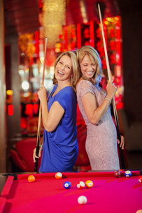 Two mature women laughing and playing pool in nightclubの写真素材 [FYI02164178]