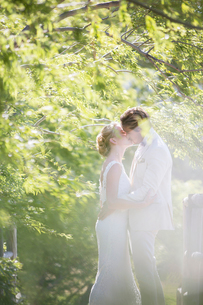 Young couple kissing in domestic gardenの写真素材 [FYI02164184]