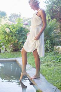 Woman dipping feet in poolの写真素材 [FYI02164200]