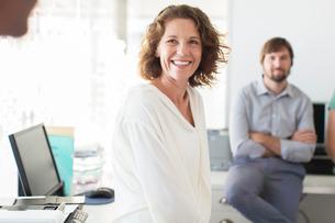 Portrait of businesswoman in office, colleague in backgroundの写真素材 [FYI02164203]