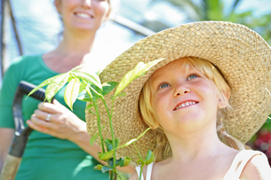 Girl wearing straw hat holding plant, woman with shovel in backgroundの写真素材 [FYI02164204]