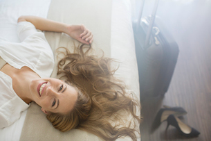 Businesswoman laying on bed in hotel roomの写真素材 [FYI02164244]