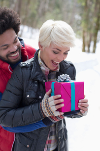 Man surprising woman with Christmas gift in snowの写真素材 [FYI02164259]