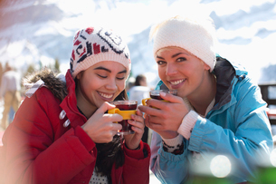 Smiling women in warm clothing drinking tea outdoorsの写真素材 [FYI02164267]