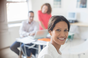 Portrait of smiling businesswoman in office, colleagues working in backgroundの写真素材 [FYI02164339]