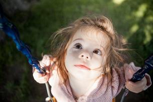 Baby girl sitting on swing outdoorsの写真素材 [FYI02164344]