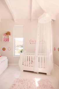 White crib with tulle canopy in pastel colored baby's roomの写真素材 [FYI02164371]