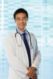 Portrait of smiling doctor wearing glasses and lab coat standing in hospitalの写真素材 [FYI02164404]