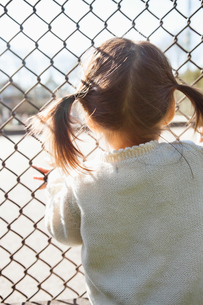 Girl standing at chain link fenceの写真素材 [FYI02164422]