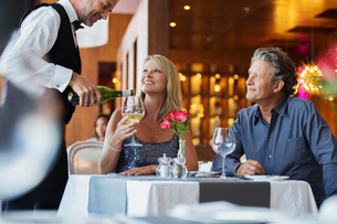 Mature couple sitting at restaurant table, waiter pouring white wine into woman's glassの写真素材 [FYI02164455]